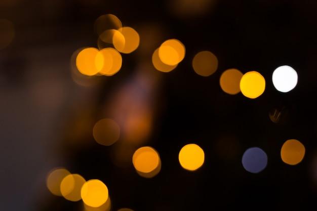 Gelber bokehkugelhintergrund. goldener feiertag leuchtender hintergrund. defokussierter hintergrund mit blinkenden sternen.