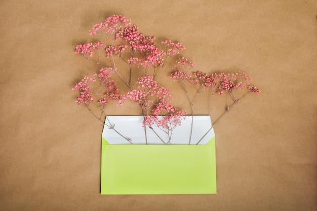 Gelber briefumschlag mit rosa blumen
