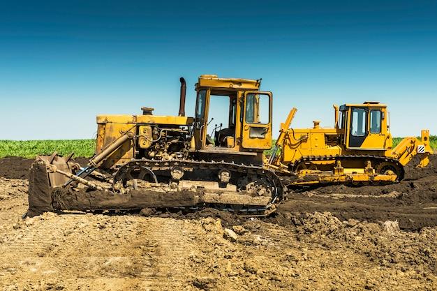Gelber bulldozer an einem sonnigen tag im feld