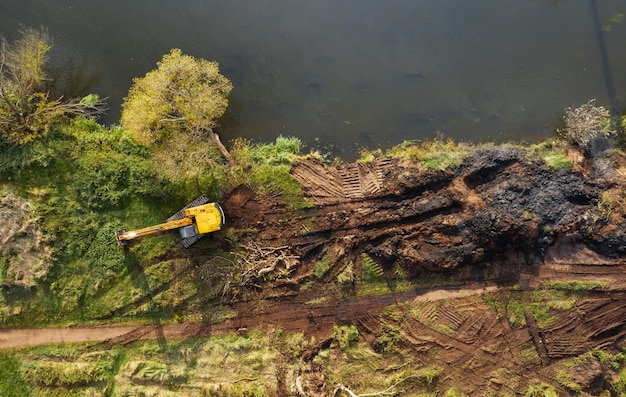 Gelber bulldozer, der einen fluss gräbt, um einen flusskanal zu vertiefen und zu säubern, um den wasserfluss zu verbessern.