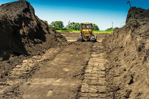Gelber bulldozer mit raupentraktor, der in einem feld steht