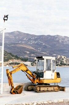 Gelber bulldozer steht an einer steinküste