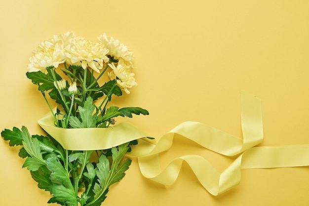 Gelber chrysanthemenblumenstrauß mit schönem breitem band auf gelbem hintergrund. grußkartenvorlage mit kopierraum