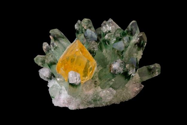 Gelber citrinkristall unter den auf schwarz isolierten grünen quarzkristallen. mineralien geologisch