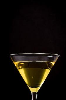 Gelber cocktail in ein glas auf schwarzer wand