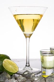Gelber cocktail in ein glas, das auf weißer oberfläche isoliert wird