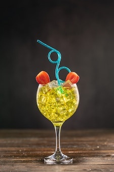 Gelber cocktail in einem mit eis gefüllten glas, verziert mit erdbeeren mit blauem flexiblem plastikstrohhalm der lockigen partei Premium Fotos
