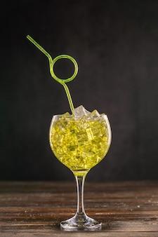 Gelber cocktail in einem mit eis gefüllten glas, verziert mit gelbem flexiblem plastikstrohhalm der gelockten partei.