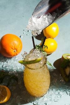Gelber cocktail mit crushed ice, dekoriert mit orange, zitrone und kiwi