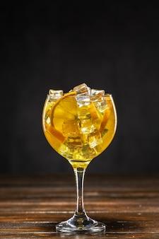 Gelber cocktail mit eis und orangenscheiben