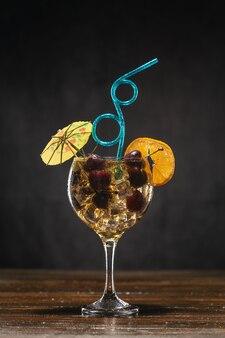 Gelber cocktail mit kirsche in einem glas, das auf einem holztisch steht, verziert mit einer orangenscheibe