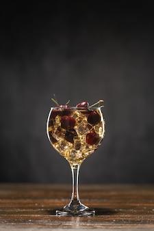 Gelber cocktail mit kirsche in einem glas, das auf einem holztisch steht