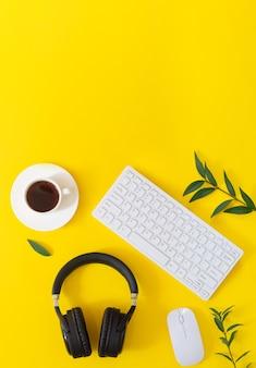 Gelber desktop mit kabellosen kopfhörern, laptop, maus, tasse kaffee und platten draufsicht. musikkonzept