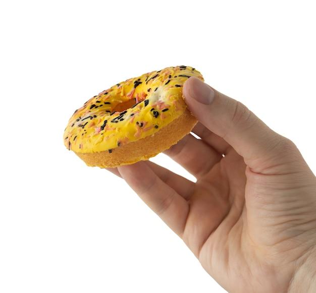 Gelber donut in der hand auf lokalisiertem hintergrund