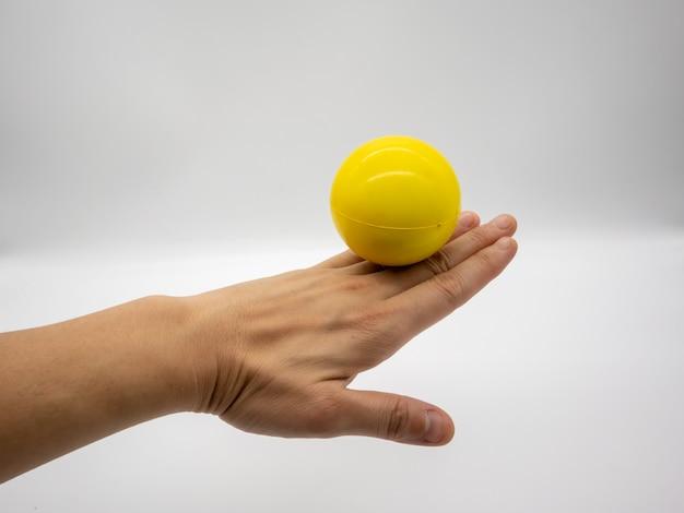 Gelber druckball bleiben auf der hinteren frauenhand, die auf weiß lokalisiert wird