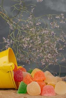 Gelber eimer mit geleebonbons mit getrockneten blumen