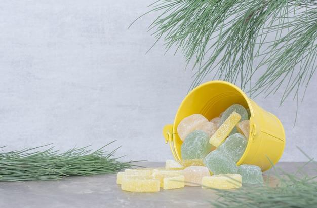 Gelber eimer mit zuckermarmelade auf marmorhintergrund.