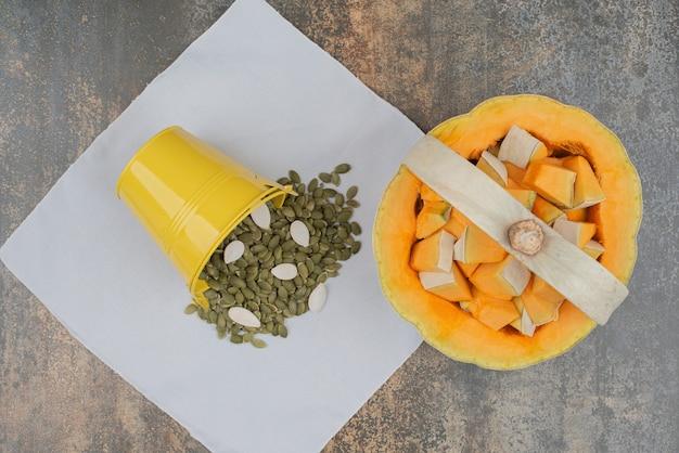 Gelber eimer voll von kürbisschalen mit frisch geschnittenem kürbis auf marmorwand