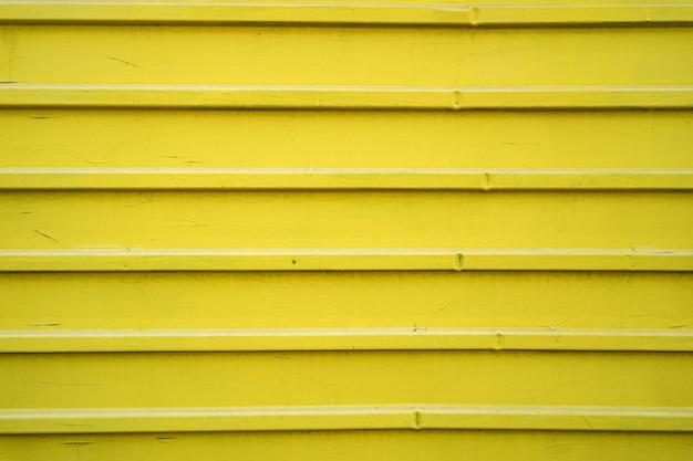 Gelber eisenzinnzaun gefütterter hintergrund. metallstruktur