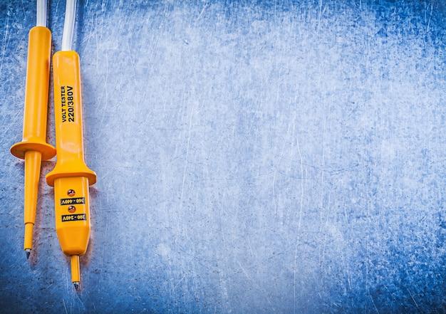 Gelber elektrischer tester auf zerkratztem metallischem hintergrundelektrizitätskonzept