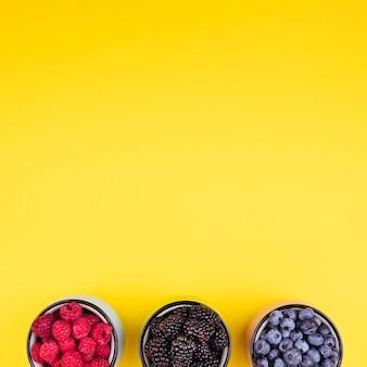 Gelber exemplarplatzhintergrund mit waldfrüchten