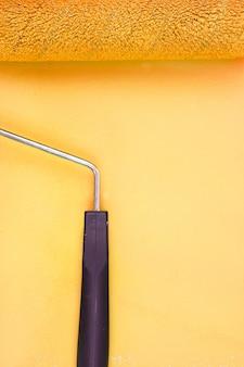 Gelber farbenrollengriff auf einem hintergrund