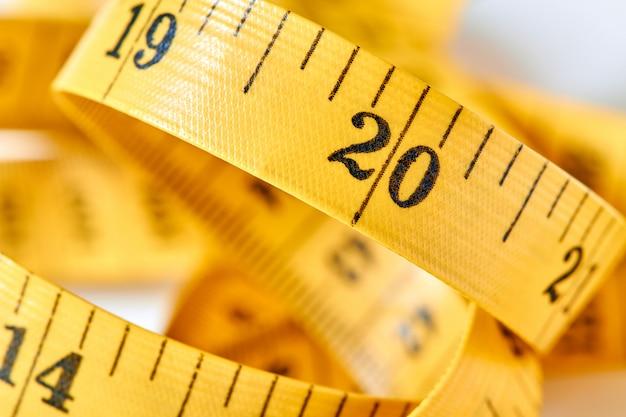 Gelber farbzentimeter mit schwarzen figuren zur messung von länge und breite auf weißem hintergrund. maßband des schneiders für sie entwerfen. nahaufnahme, selektiver fokus