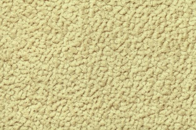 Gelber flaumiger hintergrund des weichen, flaumigen stoffes, beschaffenheit der textilnahaufnahme