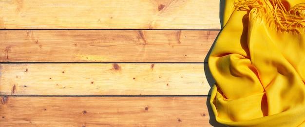 Gelber frauenschal auf holzbeschaffenheit