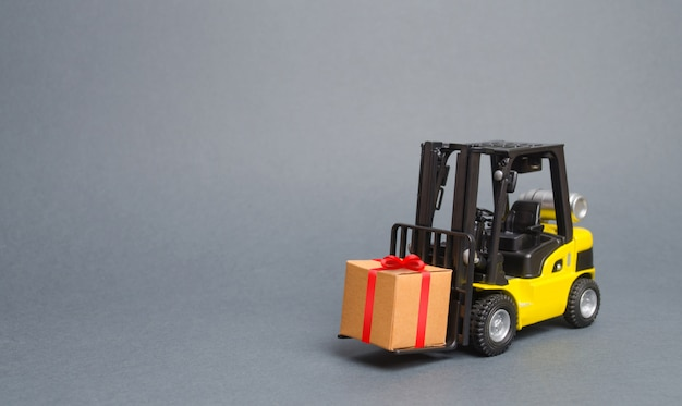 Gelber gabelstapler trägt ein geschenk mit einem roten bogen. kauf und lieferung eines geschenks. verkauf