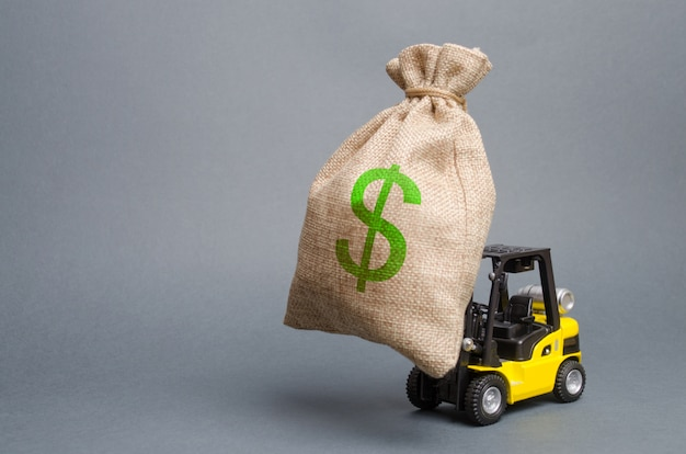 Gelber gabelstapler trägt eine große tasche des geldes. investitionen in die entwicklung anziehen
