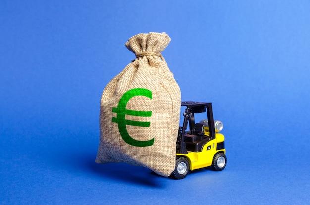 Gelber gabelstapler trägt eine große tüte euro-geld und zieht investitionen in die entwicklung an