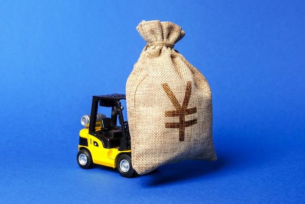 Gelber gabelstapler trägt eine tüte yen oder yuan zieht investitionen in die entwicklung an