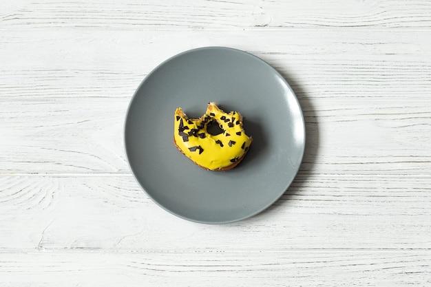 Gelber gebissener donut auf einem grauen teller, draufsicht, raum für text