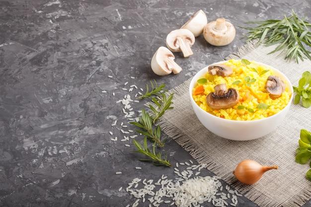 Gelber gebratener reis mit champignons pilzt gelbwurz und oregano in der weißen keramischen schüssel auf einem schwarzen konkreten hintergrund