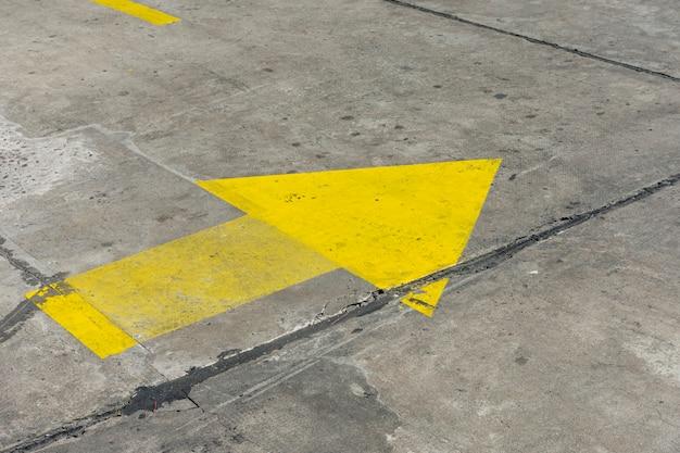 Gelber gemalter pfeil der hohen ansicht in den straßen