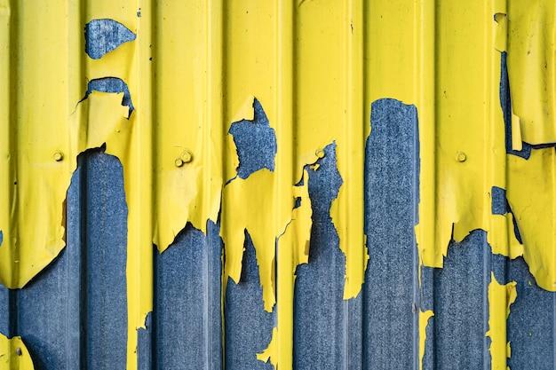 Gelber geschälter eisenzinnzaun gefütterter hintergrund. metallstruktur