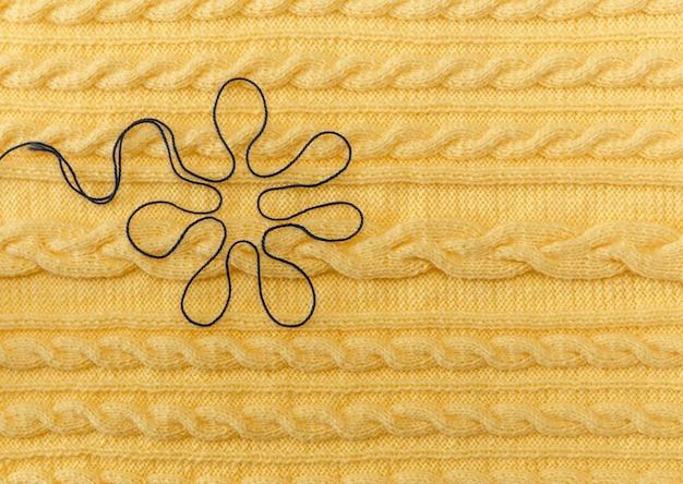 Gelber gestrickter hintergrund mit muster und zöpfen und blue floer hand made fancywork