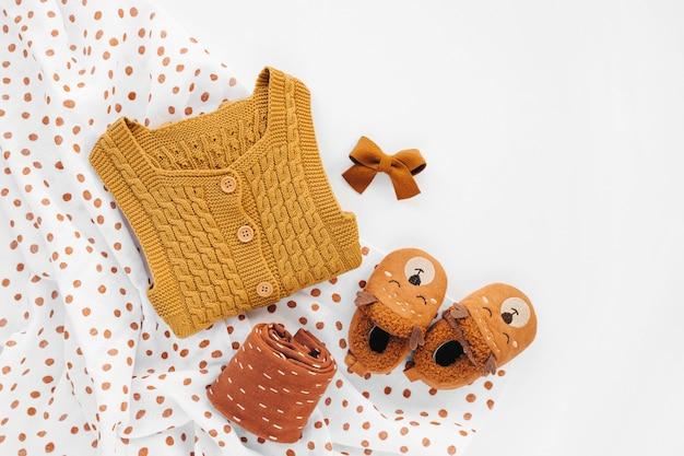Gelber gestrickter strampler, socken und süße babypantoffeln mit musselin-wickeldecke. set neugeborene kleidung und accessoires. flache lage, ansicht von oben