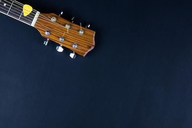 Gelber gitarrenpickel in goldenen akustikgitarrensaiten