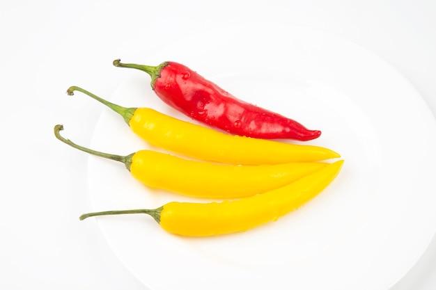Gelber, glühender chili auf einem teller. pfeffer. pflanzliche vitaminnahrung.