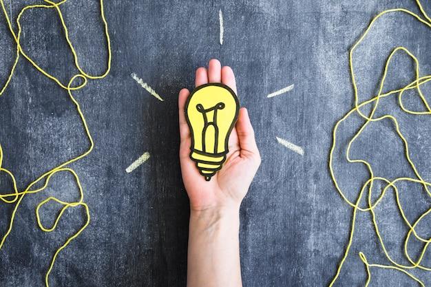 Gelber glühlampepapierausschnitt mit garn verlegen auf tafel