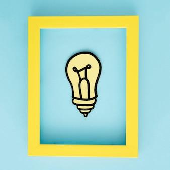 Gelber glühlampepapierausschnitt mit gelbem grenzrahmen auf blauem hintergrund