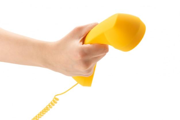 Gelber handapparat in der frauenhand lokalisiert auf weiß.