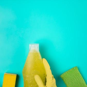 Gelber handschuh der nahaufnahme mit reinigungsmittel und schwämmen