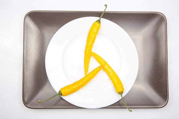 Gelber heißer chili auf einem teller. pfeffer. pflanzliche vitaminnahrung.