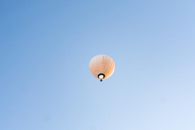 Gelber heißluftballon, der im klaren blauen himmel fliegt