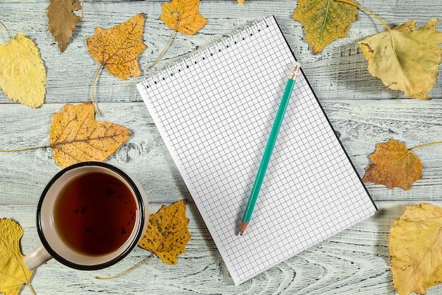 Gelber herbstlaub, eine tasse tee und ein notizbuch auf einem hellen alten hölzernen hintergrund
