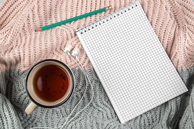 Gelber herbstlaub, eine tasse tee und ein notizbuch auf einer strukturierten strickjacke