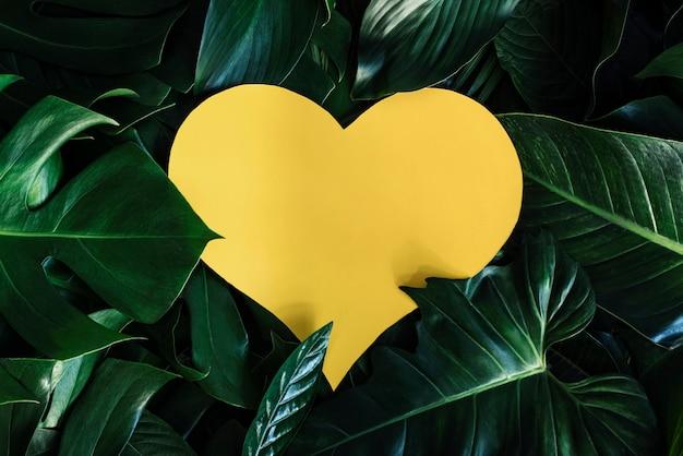 Gelber herzförmiger ausschnitt mit grünen blättern liebeskonzept legen